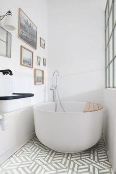 Cette baignoire ronde installée au fond de la salle de bains prend peu de place, tout en apportant une touche design à la pièce