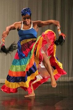 African dance - based on skirt colors and horse tails in her hands I would say she is dancing with/as/for OYA