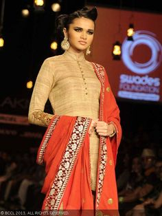 A model showcases a creation by designer Vikram Phadnis partnered with an NGO working for the empowerment of rural India, at Lakme Fashion Week (LFW) 2013