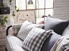 A day-bed filled with cushions in grey, white and pink