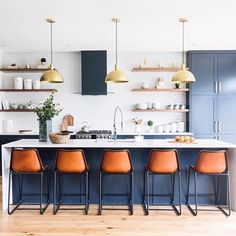 Dark blue kitchen island and units with white worktop, pendant lights and stylish leather bar seats