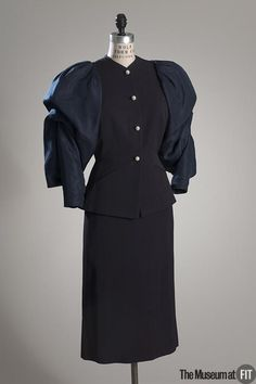 Suit | Adrian (American, 1903-1959) | United States, circa 1950 | Navy blue wool faille, silk taffeta | One of the finest designers to craft suits for women was Gilbert Adrian, the legendary Hollywood costumer-turned-fashion designer | Adrian transported suits from the silver screen to the streets of America and produced endless variations of the sharply chiseled, war-time silhouettes. This is a cocktail version, with fitted wool torso and voluminous silk sleeves | The Museum at FIT, New…