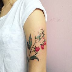 Watercolor rasperry tattoo on the left upper arm.