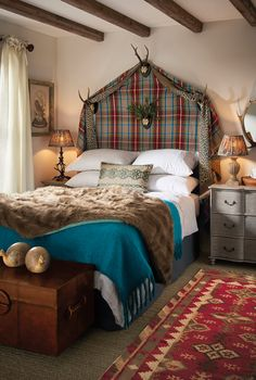 This Scottish theme bedroom by OKA is the perfect place to relax in. Bold shades of blue and red are woven into the look through a tartan headboard, traditional rug and luxurious bed throws.