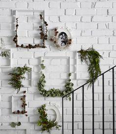 Marcos KNOPPÄNG de IKEA con algunas plantas enredadas y colgados en una pared de ladrillo blanca.