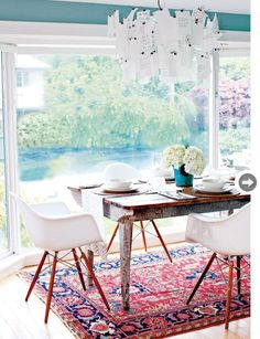 A beautiful blend of shabby, rustic glam, antique Turkish rug and the touch of mid century with crisp white Charles Eames chairs