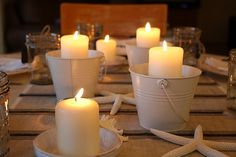 Beach party table setting with mini beach pails and candles.  Love beach pails: http://www.completely-coastal.com/2010/07/beach-sand-pails-buckets.html