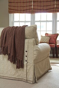 Custom slipcover with decorative trim and nail head details.