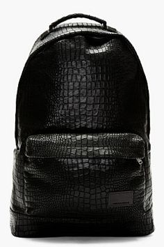 """KRISVANASSCHE // BLACK CROC ETCHED LEATHER BACKPACK  """"Croc etched leather backpack in black. Signature croco pattern etched effect throughout. Carry handle. Concealed wraparound zip closure at main compartment. Concealed zip closure at face pocket. Engraved logo plaque. Grosgrain trimmed leather adjustable shoulder straps. Slide pockets at textile lined interior. Tonal stitching. Approx. 12"""" length, 20"""" height, 4"""" width. Leather, textile."""""""