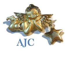 USE CODE PIN15 to get special Pinterest savings of 15% off now plus FREE shipping!  AJC cherub brooch, signed gold tone cherub brooch pin with star charm, matte and shiny finish. This adorable little guy will be quite happy perched on you chest or purse, s... #etsygifts #vintage #vjse2 #jewelry #gift