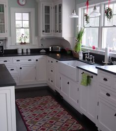 Cozy country kitchen in white with black countertops