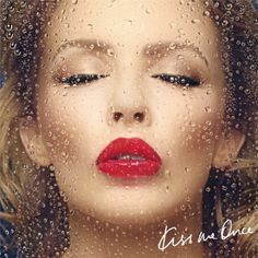 """A face portrait of a woman (Kylie Minogue) kissing a clear glass screen, with water droplets running down. A blue-ish background is behind the woman, with the text """"Kiss Me Once"""" present on the bottom right corner."""
