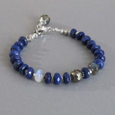 Prachtige AA faceted middernacht blauwe Lapis Lazuli, een Rainbow Moonstone, een veelzijdige pyriet en een geslepen labradoriet worden afgewisseld met handgemaakte zilveren parels. Deze armband sluit af met een kreeft-klauw gesp. Een andere mousserende faceted Pyrite gegarneerd met zilveren bloemblaadjes drops vanaf het einde van het patroon zilveren ketting. Alle metalen is.925 sterling zilver en.970 fijn zilver. Lapis - ca. 6,5 mm Rainbow Moonstone - ca. 8mm Labradoriet - ca. 8mm Pyriet…