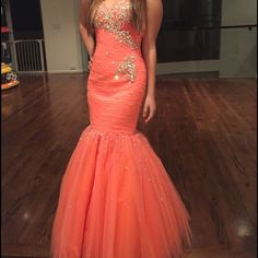Beautiful orange gown. This bright orange gown is a show stopper. It is a mermaid shape with a tulle bottom and studded with beautiful embellishments. It has a corset back and modest panel comes with it. Mori Lee Dresses Prom