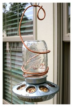 To make your own backyard bird feeder, affix a chicken feeder (which can be purchased at any hardware store) to a Mason jar filled with bird seed. Then use copper wire to create a hanger at the top.