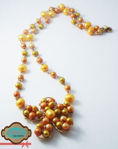Collar con flor en el centro, elaborado en gold-filled 14k y perlas cultivadas de diferentes tonos de amarillo. #Necklace