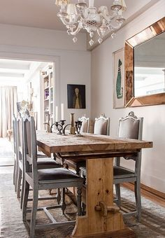 The wood of the dining table is nicely balanced by fancy chairs bought at an estate sale in New Orleans, a decorative chandelier, and a copper mirror from Marburger Farm Antique Show in Texas.