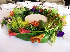 A vibrant Garland of orange, purple and red, round the bottom of a cake stand