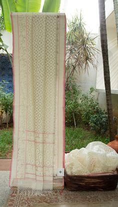 This Benares net is in porcelain white with a very interesting floral jali pattern in the body in white thread work along with silver zari highlights. The pallu and the border have elaborate floral…