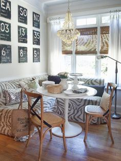 This breakfast nook features a zebra banquette, Saarinen table, capiz light and bentwood chairs.