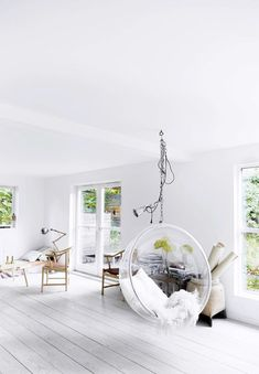 all white interior with open floor plan and transparent bubble chair hanging from a chain. Diy Crafts On A Budget, White Wood Furniture, Furniture Ideas, Clear Chairs, Hanging Chairs, Bubble Chair, White Beams, Painted Floors, Swinging Chair