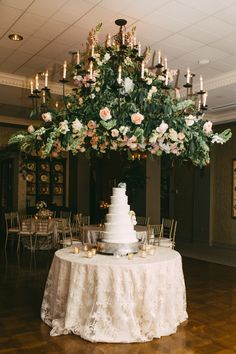 Chandelier covered in greens and roses, romantic florals above the wedding cake // Kelly Ginn Photography