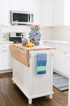 Crisp white cabinets and countertops pop against a rich wood floor. See Lemon Stripes' kitchen reveal for all the details. Diy Kitchen Island, Kitchen Reno, Kitchen And Bath, New Kitchen, Kitchen Design, Kitchen Remodeling, Kitchen Ideas, Kitchen Cabinets, Luxury Kitchens