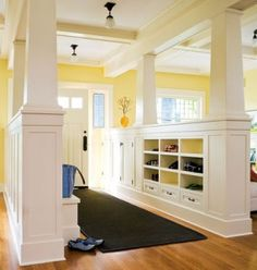 All the perks of a mudroom! Idea for what to do in the downstairs room - love the pillars and half wall that divide the mudroom and living room.