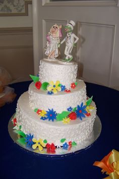 tipsy wedding cake with scroll piping and bright blue, yellow and red whimsy sugar flowers. Miss Piggy and Kermit the Frog Muppets topper
