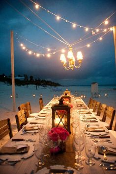 This Breathtaking Coastal Style Outdoor Candlelight dinner with Long Table with candle decor as well as Chandelier and String Lights Decor over the table
