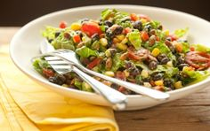 Black Bean Salad With Avocado-Lime Dressing  1 ripe avocado, mashed 1/4 cup chopped cilantro 2 tablespoons lime juice 2 (15 ounce) cans no-salt-added black beans, rinsed and drained 4 cups shredded romaine lettuce 1 cup grape tomatoes, halved 1 cup corn kernels, fresh or thawed if frozen 1 small red bell pepper, chopped 1/2 cup toasted pumpkin seeds