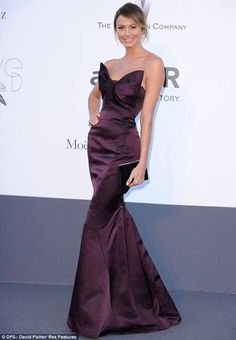 Stacy Keibler stunned in a purple gown featuring a huge bow as she attended the amfAR Cinema Against Aids gala as part of the Cannes Film Festival on Thursday