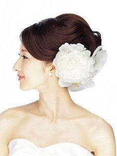 ふんわり流した前髪からつながるように後頭部に大きなアップをつくります。トップの位置を低めにすると落ち着いたイメージに。生花はコチョウランとシ...