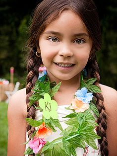 Create a custom lei for each child to wear during the party. Use a large flower punch to make a paper flower from cardstock, write the kid's Hawaiian name on top, and attach to a leafy lei.