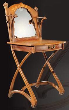 LOUIS MAJORELLE (1859-1926) Rare coiffeuse en acajou et chêne à plateau rectangulaire cintré en façade, à décor marqueté en bois exotiques figurant des abeilles et des fougères, ouvrant en ceinture par un tiroir à poignée en bronze doré. En partie haute elle présente un miroir orientable à découpe ondulée à décor marqueté d'iris, flanqué de deux tablettes circulaires terminées par des graines sculptées.vers 1900
