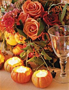 accent centerpieces that include autumnal-hued roses hydrangeas and scabiosa pods with some miniature pumpkin pear and apple votives