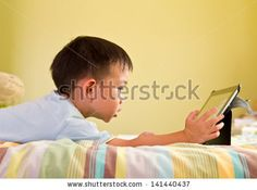http://www.shutterstock.com/pic-141440437/stock-photo-chinese-boy-using-tablet-while-lying-on-bed.html?src=FHlC6Ti-yAtPmROzRyiSdA-2-42