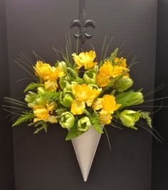 Spring Season 2014 Wall Hanging: Mint Green Tulips, Yellow Irises and long wild grass blades on a white wall planter, held by Black metal Fleur De Lis wreath hanger. Design and Arrangement by http://nfmdesign.synthasite.com/