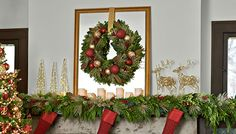 Christmas fireplace decorations include a decorated wreath hung on a mirror, garland, LED candles and shiny reindeer.