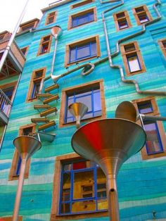 In Germany a large, multi-story blue building houses the funnel wall attraction designed by three collaborative artists including Christoph Roßner, Annette Paul, and Andre Tempel. The three artists knew that the building needed to have rain gutters, so why not get a bit creative? This system of mousetrap drain and gutters features various sized metal cones that play music when it rains.