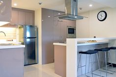 To complement the white countertops that the lady of the house requested, Nicca chose tan-colored, high-gloss laminate modular kitchen cabinets that add a subtle hint of color to the space. They also used non-porous solid surfaces instead of natural stones for easier maintenance.�