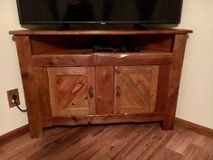Custom corner TV stand made from beetle kill rough sawn lumber and aged with a technique using steel wool soaked in vinegar.