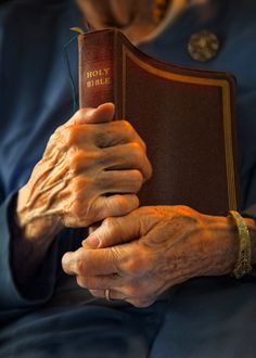 Enduring Comfort, old hands holding a bible