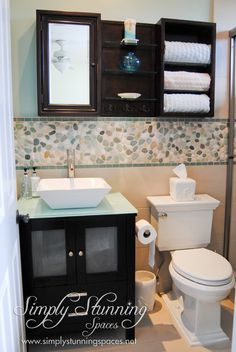 Simply Stunning Spaces bathroom design. Backsplash inspiration! We love how this turned out; the contrast of the dark cabinetry with the backsplash is idyllic. Also, the wall cabinets are optimized for organizational purposes. For more interior design inspiration visit: http://simplystunningspaces.com/
