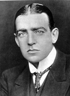 Man with hair centre-parted, wearing high white collar with tie, and a dark jacket. His facial expression is serious