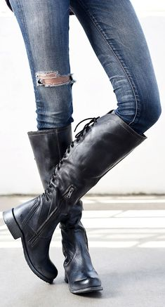 These handmade black leather knee-high boots by BEDSTU feature lacing up the entire back for a unique feminine touch.