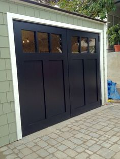 Garage door style Craftsman style swing out carriage garage doors.