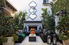 At home with Khloé and Kourtney Kardashian: In the courtyard at Khloé's house, the fireplace surround is clad in tile designed by Martyn Lawrence Bullard for Ann Sacks; the mirror is by RH.