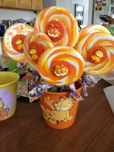 Orange swirl lollipops with a Garfield embellishment  added  on the outside of wrapper.