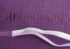 Insira a agulha com 2 fitas, uma lilás e outra lilás mescla, avesso com avesso, após os 4 primeiros fios do segundo passante.